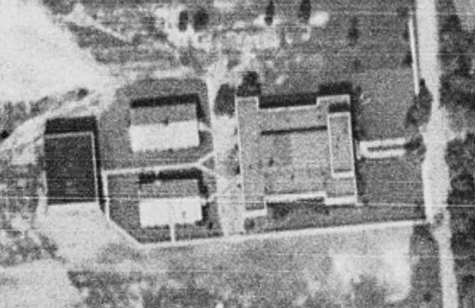 Black and white aerial photograph of Herndon High School taken in 1937. The building is shaped like the letter 'I'. The two vocational classroom buildings and gymnasium are visible at the rear of the building. There are cement walkways connecting the buildings to one another.