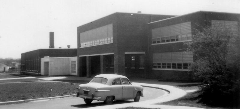 Black and white photograph of the new Herndon High School addition in 1954 from the Fairfax County School Board's fire insurance survey. It is a long, rectangular, brick building with windows on all sides. A small 1940s era car is parked in the driveway circle in front of the school.
