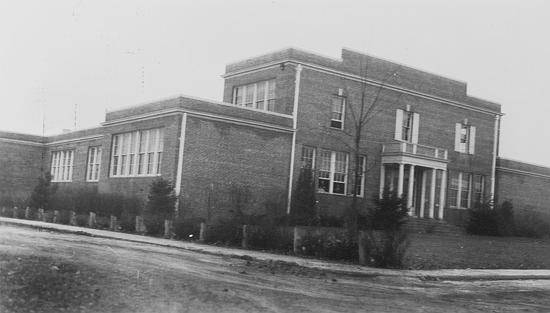 Black and white photograph of 1927 Herndon High School Building, believed to have been taken in March 1937 by a photographer with the Virginia Department of Education. The building is mostly one-story, but there is a two-story section near the front entrance. The building is made of brick and is very boxy in shape. There is an elegant main entrance with a portico of white columns.