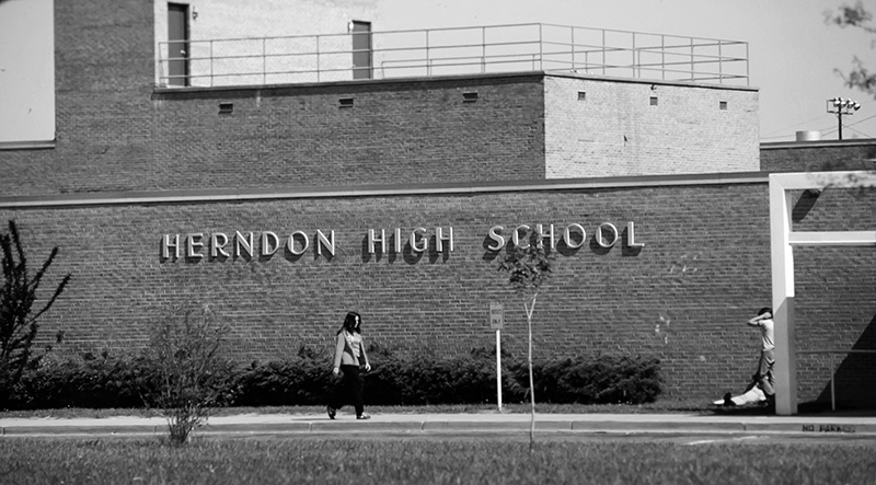 Black and white photograph of the front of Herndon High School's 1967 building. The name Herndon High School is attached to the brick façade. One student can be seen walking along the sidewalk and two more can be seen on the far right side of the image.