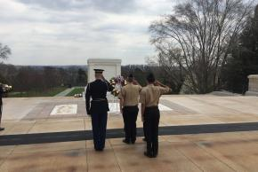 Three cadets in front of a memorial